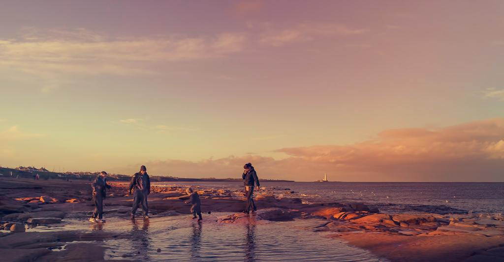 family walking on seashore during golden hour